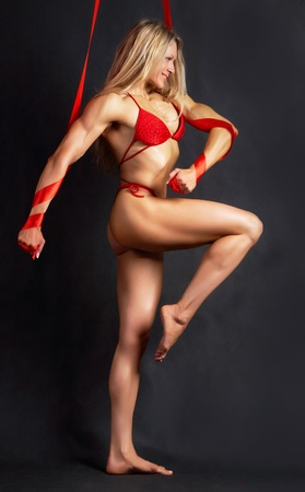 A beautiful model in red bikini marching to the right with red ribbons wound round her arms photo