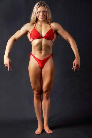 A beautiful woman bodybuilder posing in red bikini photo