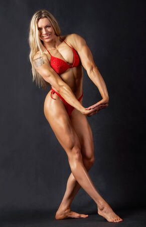 A beautiful woman bodybuilder posing in red bikini and smiling photo