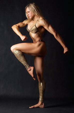 A beautiful woman bodybuilder in bikini marching  photo