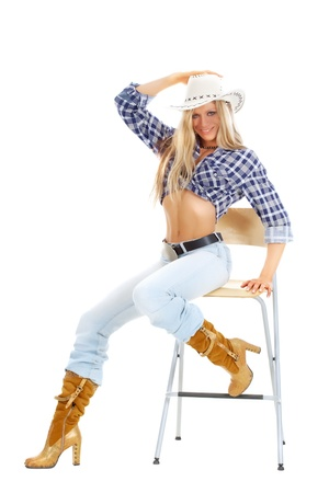sexy cowgirl: Portrait of a sexy woman in American cowgirl clothing posing on a chair  Stock Photo