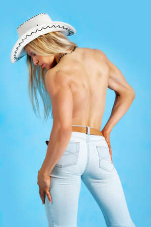 Rear view of a topless woman posing in jeans and cowboy hat photo