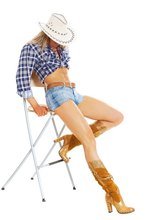 wearing: Portrait of a sexy model posing in cowgirl clothing posing on a chair  Stock Photo