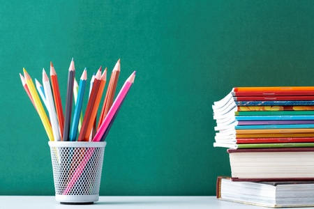 Image of crayons and exercise books against blackboard  Stock Photo - 9402670