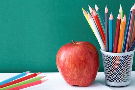 Image of crayons and red apple against blackboard photo