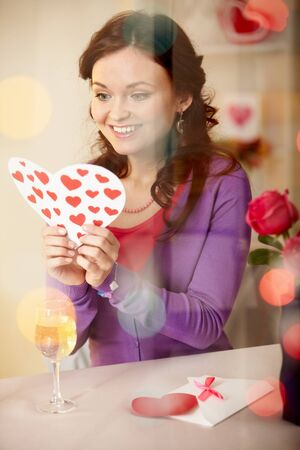 A young girl in restaurant holding Valentine card  photo