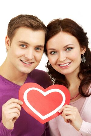 corazon: Portrait of a young beautiful couple holding paper heart and smiling