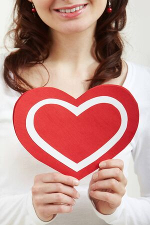 corazon: Close-up of female hands holding paper heart