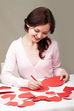 crafts person: Portrait of a woman signing valentine cards