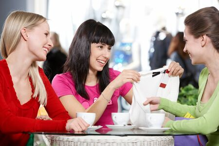 Three young women sitting in cafe and discussing new purchase Stock Photo - 9410517