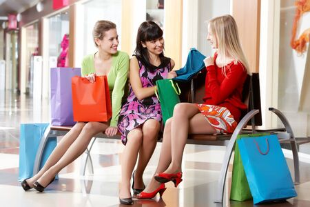 Three girls sitting in shopping mall and showing new clothing  photo