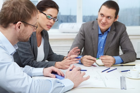 Three businesspeople sitting at table and making a draft Stock Photo - 9410530