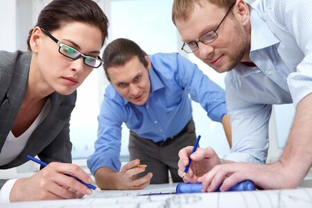bending over: Three businesspeople with pencils bending over a draft Stock Photo