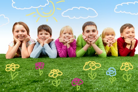 Group of happy children lying on a green grass photo
