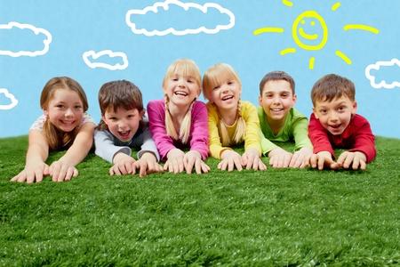 lying in grass: Grupo de ni�os felices acostado sobre una hierba y que se extiende sus manos