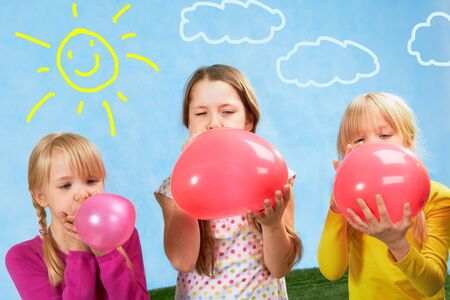 inflating: Photo of three cute girls inflating balloons