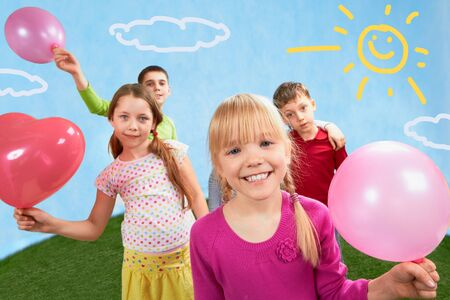 Image of children holding balloons with girl in front   photo