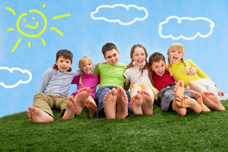 Group of happy children relaxing on the grass together photo