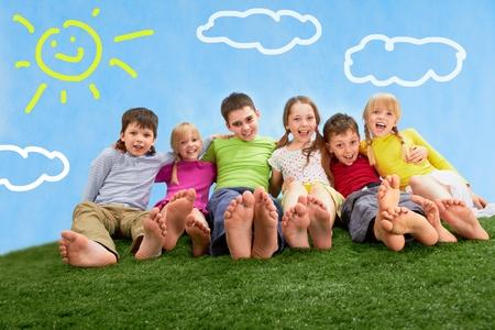 Grupo de niños felices juntos de relajación en la hierba