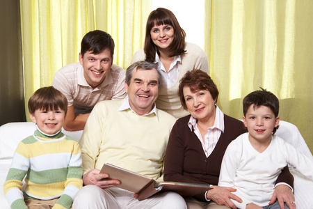 Portrait of happy family of six sitting on sofa and looking at camera photo