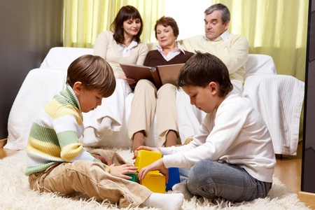 Family of grandparents and mother sitting on sofa and reading and two boys playing together  photo