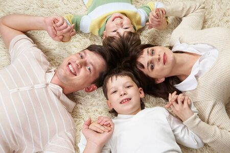 A happy family holding on carpet with clutched hands photo