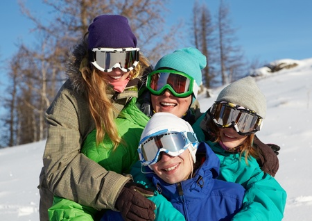 Portrait of four young people in ski goggles embracing  photo