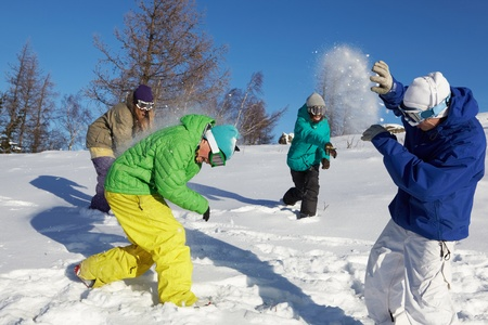 Four teenagers throwing snowballs outdoors  photo