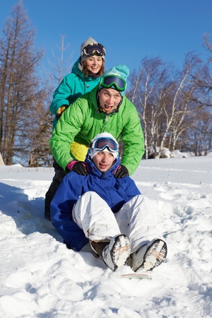 Two teens pushing their friend sitting on a snowboarder  photo
