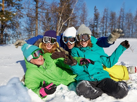 Portrait of four laughing teenagers in ski goggles sitting on snow photo