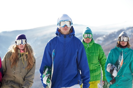 Four people in ski goggles carrying snowboards  photo