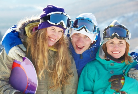 Portrait of three cheerful friends in ski goggles looking at camera and smiling photo
