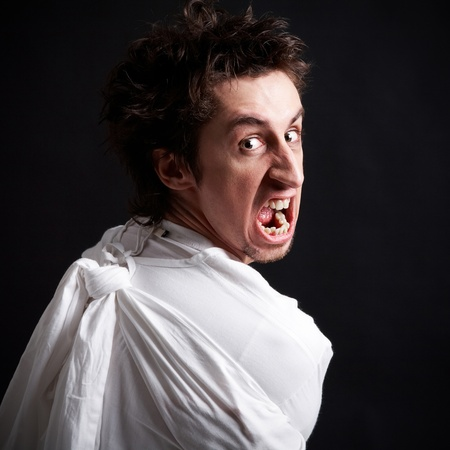 hospitalized: Insane man in strait-jacket screaming in isolation Stock Photo