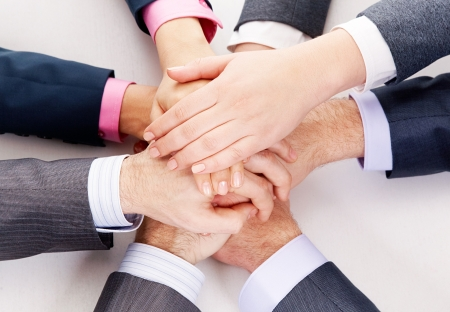 handskakning: Image of business people hands on top of each other symbolizing support and power