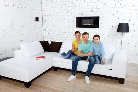 A young family relaxing on sofa and looking at camera in new house photo