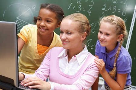 Portrait of two girls and teacher looking at the laptop in classroom  photo
