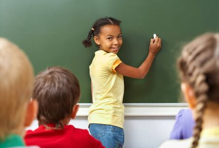 classmate: Image of schoolgirl by the blackboard looking at camera through classmates   Stock Photo