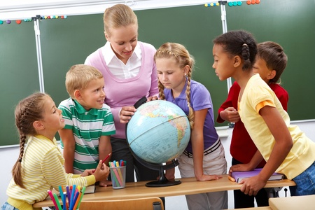maestro: Retrato de alumnos mirar el mundo escuchando al profesor durante la lecci�n de geograf�a Foto de archivo