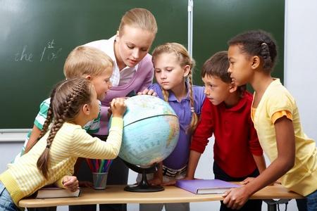 school teachers: Retrato de alumnos mirar el mundo escuchando al profesor durante la lecci�n de geograf�a Foto de archivo