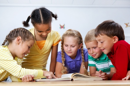 kids reading book: Portrait of pupils looking at page of encyclopaedia at reading lesson