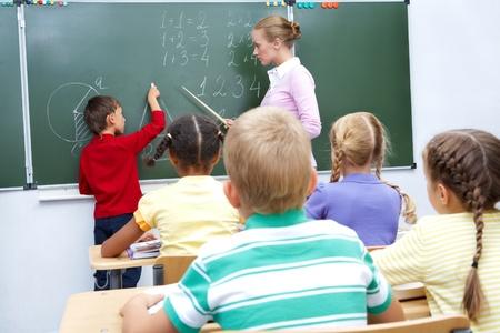 ni�os escribiendo: Foto de estudiante de primaria por pizarra mirando su profesor le ayuda