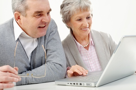 Portrait of attractive grandmother and grandfather studying to use laptop  photo