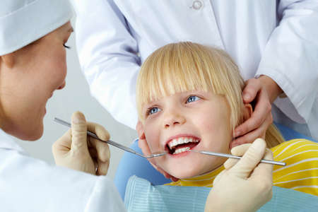 dental medicine: Image of little girl having her teeth checked by doctor and assistant
