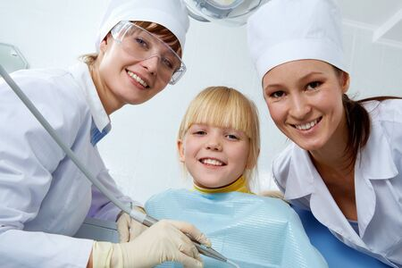 Group of dentist, assistant and little girl looking at camera   Stock Photo - 9455284