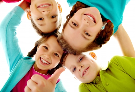 elementary kids: Photo of joyful children touching by their heads with girl her thumb up