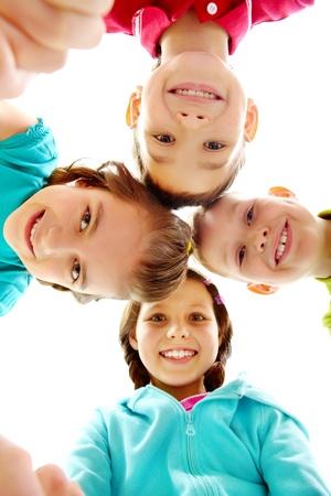 Company of four joyful children looking at camera  photo