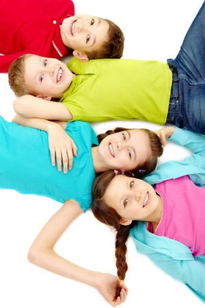 elementary kids: Group of happy small friends lying in line  Stock Photo