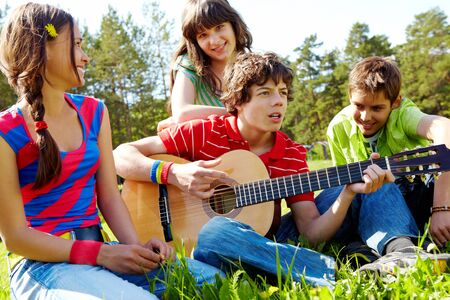 Portrait of handsome lad playing the guitar surrounded by his friends photo