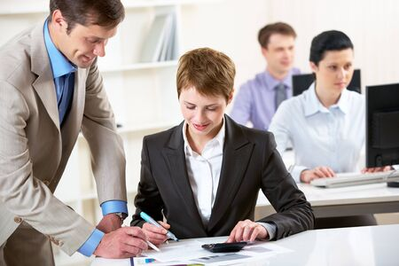 Portrait of businessman consulting pretty employee at meeting Stock Photo - 9537339