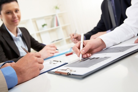 business deal: Close-up of business person hand over document in working environment Stock Photo